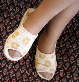 Two legs with elastic stockings and slippers on a carpet.